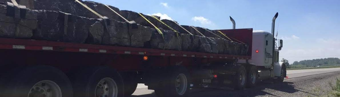 Daily armour stone delivery by flatbed truck in Ontario