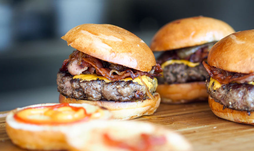 Closeup of hamburgers with bacon and cheese