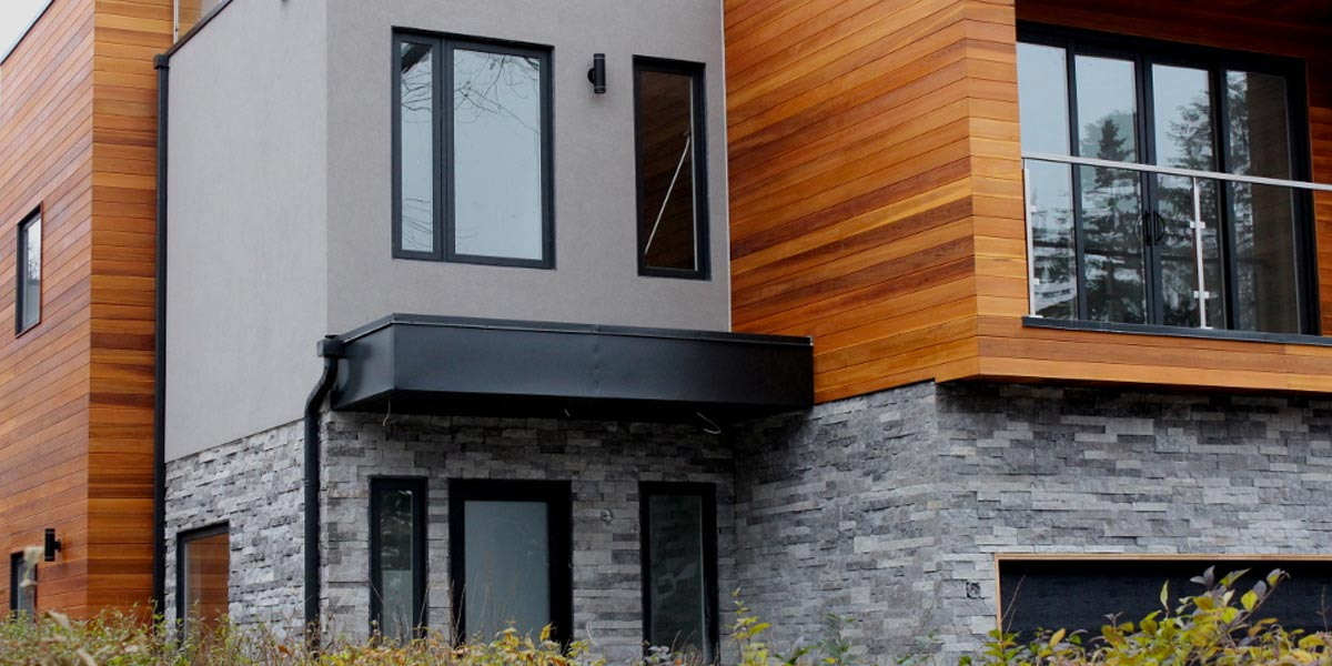 Montrose Grey veneer stone on modern home with black and wood elements