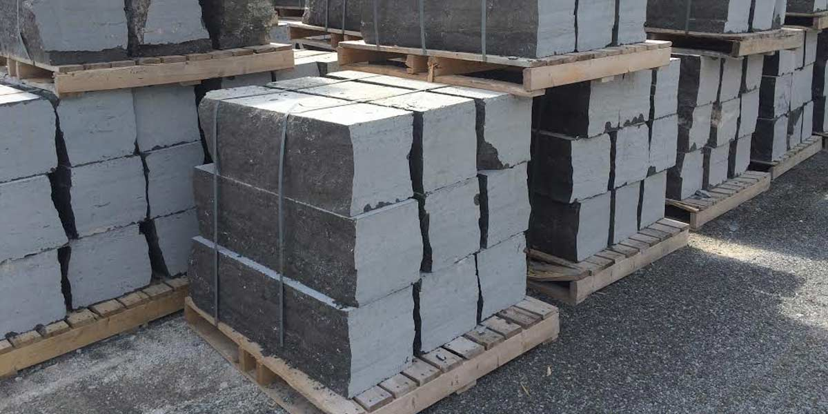 "Sawn Armour 12"" x 12"" armour stone stacked on skids in yard"