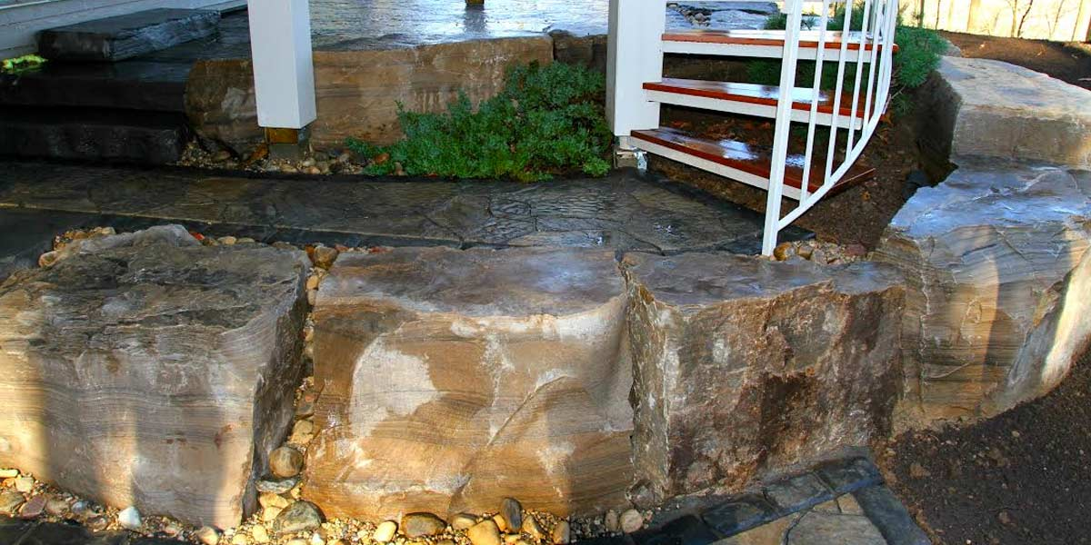 Skidded Wiarton armour stone bordering circular patio